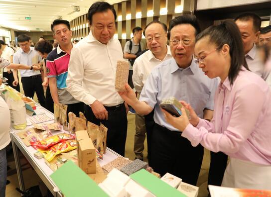 出席领导在电商扶贫品牌推介产品展示现场了解农特产品情况